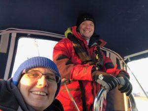 Glückliche Menschen bei kalten Wetter auf einem Segelboot